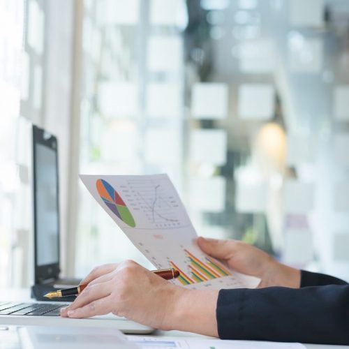 Startup business woman working with business documents on office table with graph financial diagram. Business idea concept.