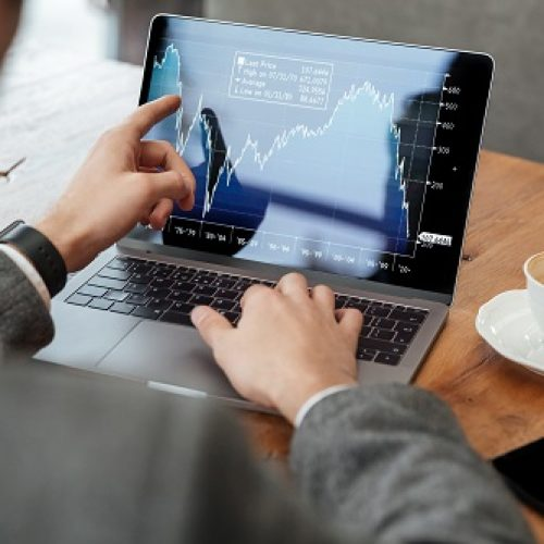 Cropped image of business man sitting by the table in cafe and analyzing indicators on laptop computer